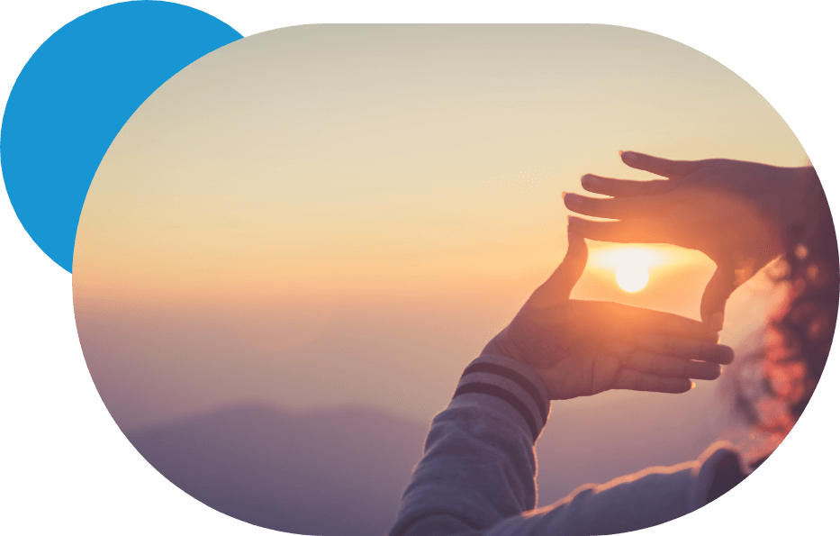 Persona encuadrando el sol con las manos.